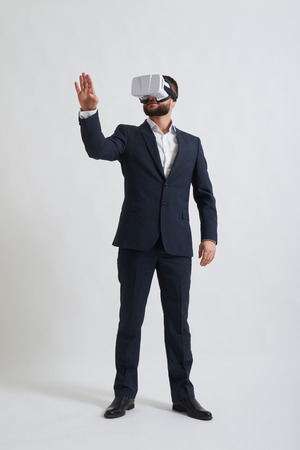 formal wear: Businessman in a formal wear and virtual reality glasses is trying to touch something in front of him
