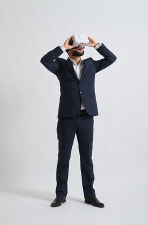formal wear: Businessman in a formal wear is watching something using virtual reality glasses