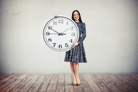 businesswoman suit: A young smiling woman in checkered dress is holding a big round clock in her hands Stock Photo