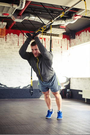 facing away: A young sportsman in training suite is doing a stand facing away on the suspension trainer Stock Photo