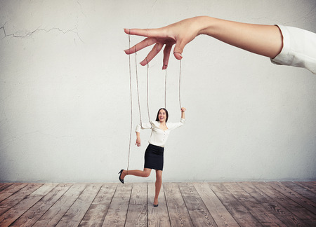 Młoda kobieta ciemnych słyszymy w białej bluzce i czarnej spódnicy porusza się jak marionetka, podczas gdy duża dłoń nad nią ciągnie za sznurki
