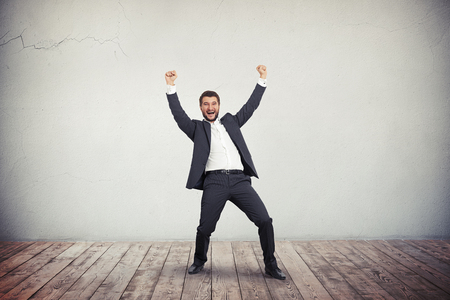 gray suit: A young man in grey business suit is vigorous and joyful apparently he succeeded in something