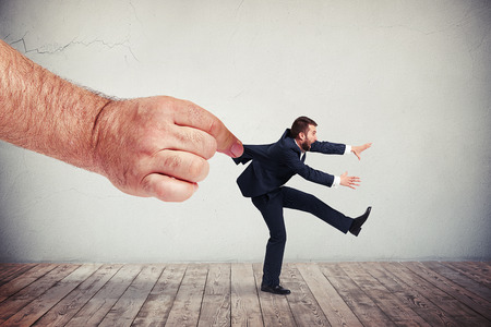 vigorously: A big males hand is pulling a man in in dark grey business suit backwards while the man is vigorously trying to resist Stock Photo