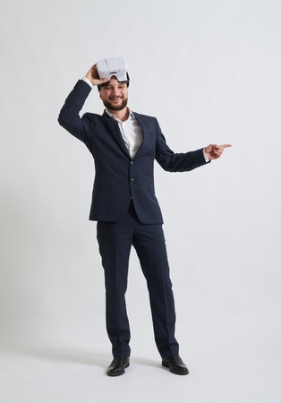 formal wear: Businessman in a formal wear and virtual reality glasses is smiling and pointing at something on his left