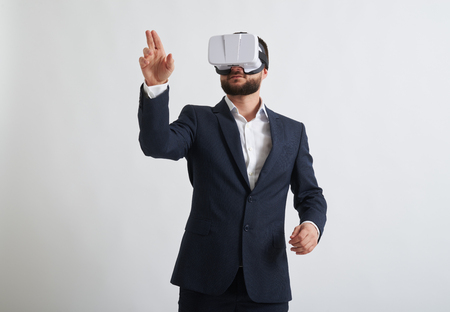 formal wear: Close up of businessman in a formal wear and virtual reality glasses who trying to touch something with his hand Stock Photo
