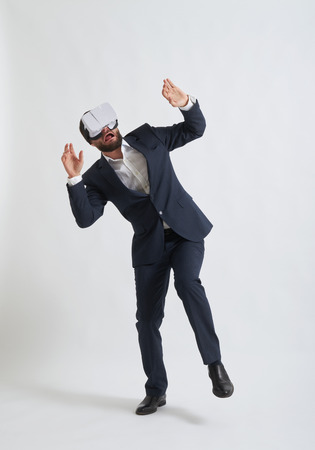 scaring: Businessman in a formal wear and virtual reality glasses scaring something Stock Photo