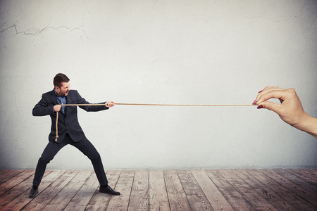 vigorously: A man in dark business suit is vigorously pulling the rope from the one end while a females hand is holding another end of the rope Stock Photo