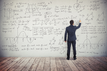 algebraic: A man in dark business suit is drawing algebraic graphics geometry figures on the white wall and writing down formulas to solve these different mathematical tasks Stock Photo