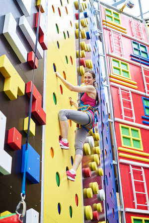 safety harness: A smiling young woman in safety harness is climbing on a high rock-climbing wall in gym