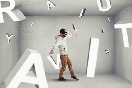man shirt: Man in virtual reality glasses is stepping carefully between flying letters composing word combination virtual reality in room with white walls and floor