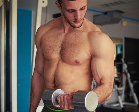 nackte brust: Junge starken Mann mit nackten Brust hebt eine Hantel Lizenzfreie Bilder