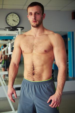 nackte brust: Junger muskul�ser Mann mit nacktem Oberk�rper im Fitness-Studio stehen