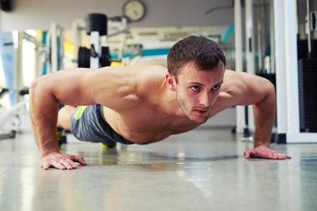 nackte brust: Junge gesunde Mann mit nackten Brust macht Push-ups �bungen im Fitness-Studio Lizenzfreie Bilder
