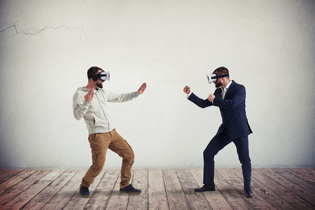 Two men, one in casual clothes, another in dark business suit, are wearing virtual reality glasses and combating in virtual reality in white room with wooden floor Banque d'images