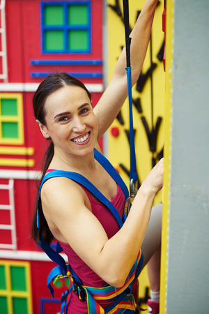 recreational climbing: Close-up of a young fit smiling woman in safety harness who is climbing on the wall in indoor rock-climbing center Stock Photo