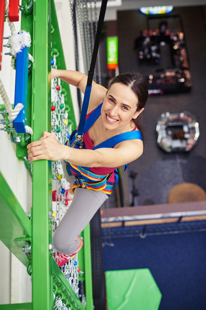 recreational climbing: Young smiling sportswoman in safety harness is climbing high on the wall in indoor sport center