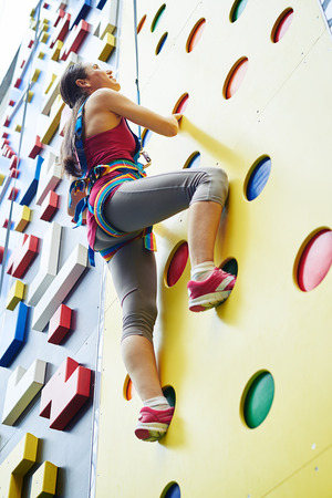 safety harness: A young woman in safety harness is looking upwards while climbing on the artificial rock-climbing wall