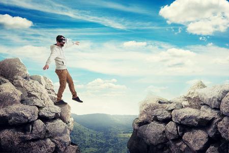 Hombre de las gafas de realidad virtual está intensificando cuidadosamente para caminar en el aire entre dos rocas altas en valle soleado Foto de archivo