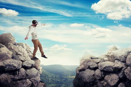 Man in virtual reality glasses is stepping carefully to walk on air between two high rocks on sunny valley Stock Photo