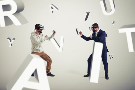 business letters: Two men, one in casual clothes, another in dark business suit, are wearing virtual reality glasses and standing in fighting poses ready to start their combat in virtual reality surrounded by flying letters