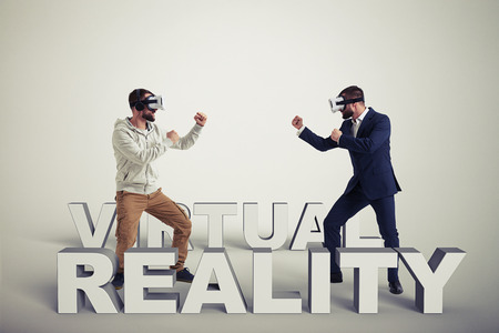 3d dimensional: Two men, one in casual clothes, another in dark business suit, are wearing virtual reality glasses and standing in fighting poses ready to start their combat in virtual reality, they are standing on grey background between 3d dimensional letters composing Stock Photo