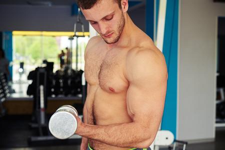 nackte brust: Junge starke Mann mit nackten Brust h�lt Hantel und lockern, wodurch Bizeps in der Turnhalle