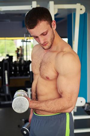 nackte brust: Passender Mann der Junge mit nacktem Oberkörper hält Hantel und lockern, wodurch Bizeps in der Turnhalle Lizenzfreie Bilder