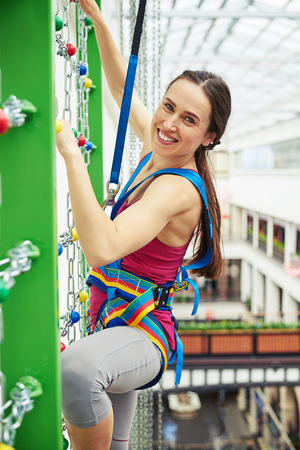extreme sports: Sportswoman in safety equipment is smiling while climbing on the wall with chains in indoor rock-climbing center Stock Photo