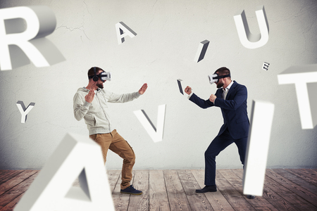 business letters: Two men, one in casual clothes, another in dark business suit, are wearing virtual reality glasses and standing in fighting poses ready to start their combat in virtual reality in empty room with grey walls and wooden floor surrounded by flying letters Stock Photo