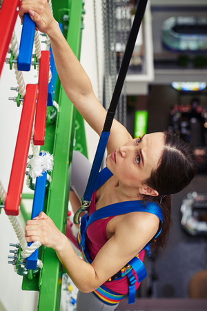 rockclimbing: Close-up of a sportswoman who is climbing on the wall in indoor rock-climbing center