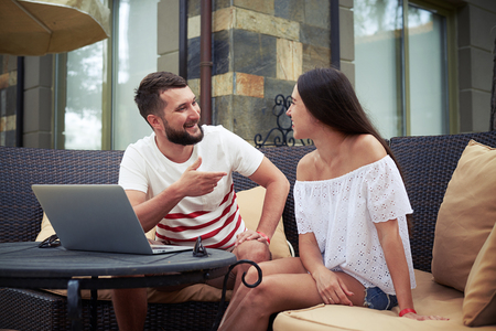 vividly: Beautiful woman and young bearded man are sitting on open terrace in the yard and vividly discussing something near laptop Stock Photo