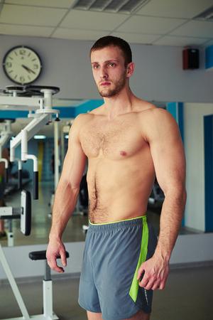 nackte brust: Junge gesunde muskulöser Mann mit nacktem Oberkörper und in grauen Shorts ist im Fitness-Studio stehen