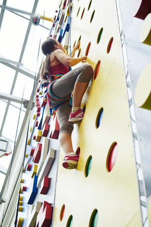 safety harness: Young woman in safety harness is climbing on the wall in indoor rock-climbing center