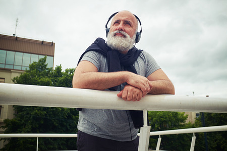 handhold: Stylish aged man in headphones is leaning on the handhold and looking up in the sky on a cloudy summer day