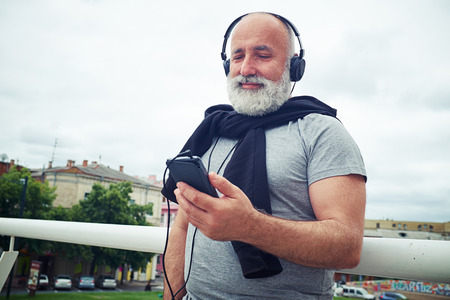 handhold: Stylish aged man in casual clothes is standing near handhold on the bridge wearing headphones connected to his smart phone