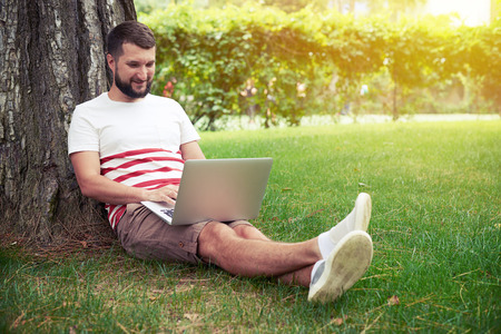 man sit: Young smiling bearded man is sitting on green grass under the tree and typing on his laptop