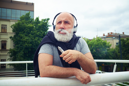 handhold: Stylish aged man in headphones is leaning on the handhold and smoking electronic cigarette on a cloudy day in city Stock Photo