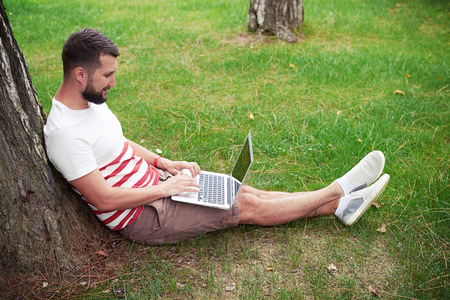 people relaxing: Young bearded man is sitting on green grass under the tree on the garden and working in his laptop Stock Photo