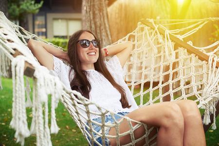 Junge lächelnde Frau mit dunklen hören in Sonnenbrille entspannt unter warmer Sonne sitzt in Hängematte im Garten Standard-Bild