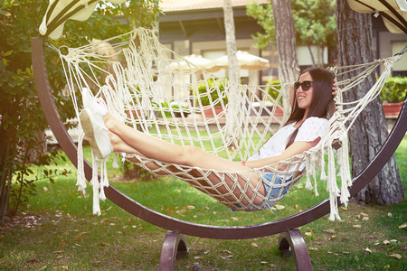 recreational: Young smiling woman with dark hear in sunglasses is resting in hammock in the backyard