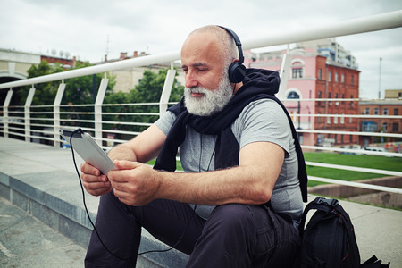 white man: Stylish aged man with white beard is sitting on a sidewalk on the bridge and watching something on his tablet computer in headphones