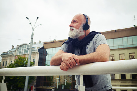 musing: Stylish aged man in headphones is leaning on the handhold and musing in the city on a cloudy day