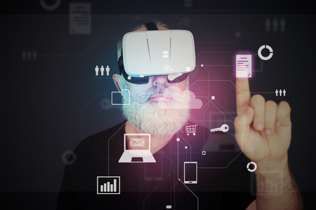 wearable: Aged bearded man in 3d virtual reality glasses over dark background is clicking on white virtual icon Stock Photo