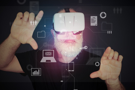 zooming: Aged bearded man in 3d virtual reality glasses over dark background is zooming the virtual reality screen with his hands