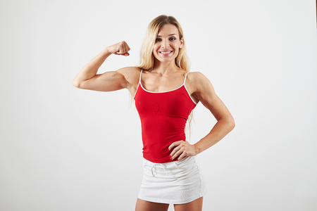showing muscles: Sexy female bodybuilder in red top and white skirt is posing and showing muscles isolated over white background Stock Photo