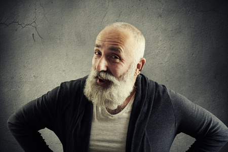 white beard: Smiling aged man with white beard in stylish casual clothes is posing at the camera with hands on hips against grey concrete wall
