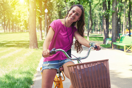 Portrait of beautiful dark-haired woman on a bicycle with basket on alley in the park
