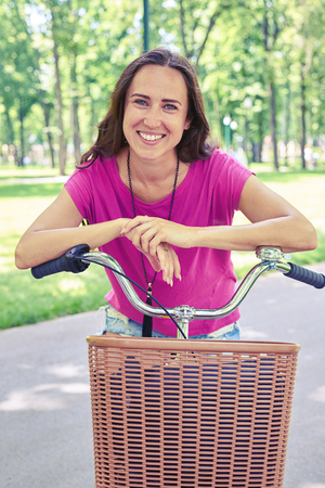 recreational area: Close-up of smiling beautiful woman who is posing on bicycle with basket in recreational area
