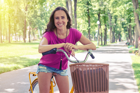 sunlit: Smiling beautiful female in casual clothes is posing on bicycle on sunlit parkway Stock Photo