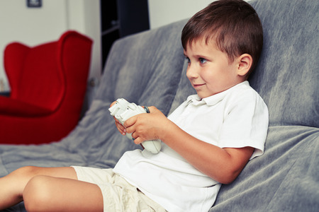 Small boy is rapt in playing a videogame using a joystick sitting on a cozy grey sofa